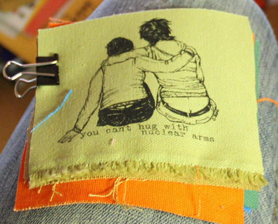 "patch with image of two people with arms around each other and the text: ""you can't hug with nuclear arms"""