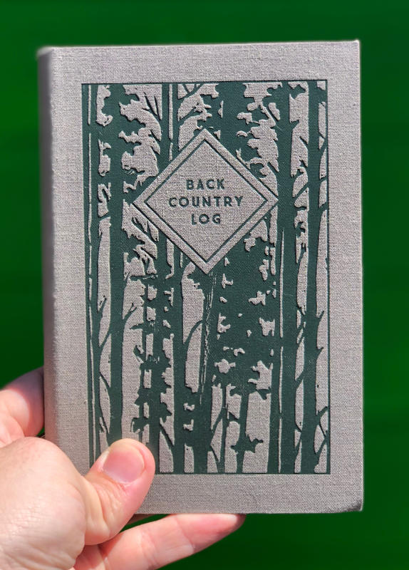 a cool grey cover with the silhouette of trees across the front
