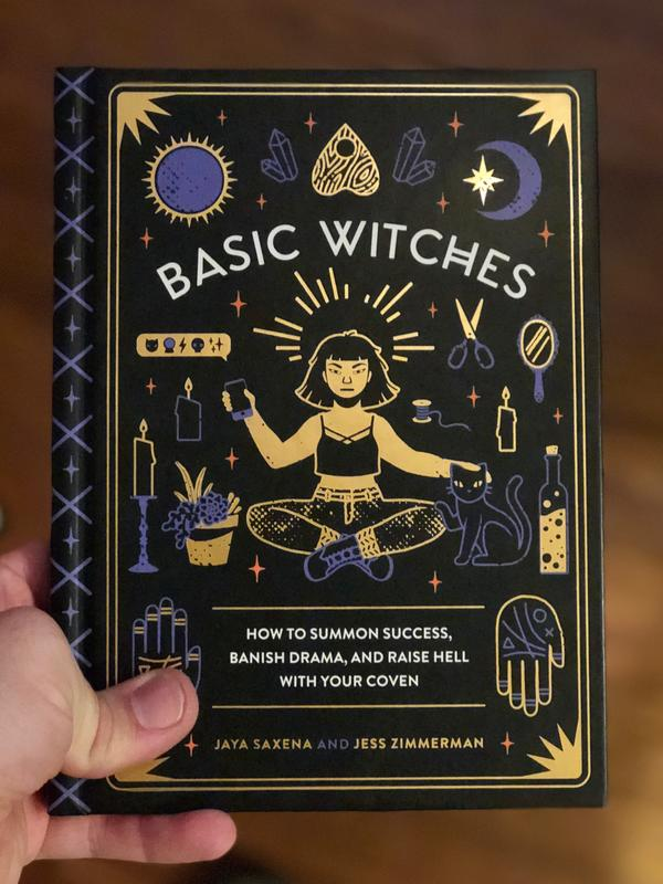 Cover of Basic Witches which features a person sitting cross-legged and holding a smart phone. They are surrounded by a variety of traditionally witchy symbols like a candle and a cat