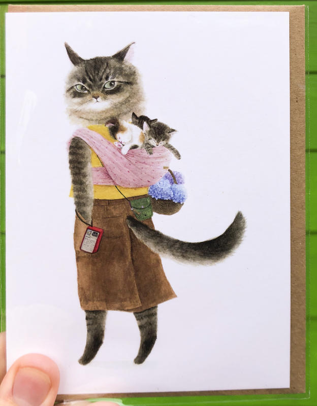 A grey cat wearing a papoose on her back filled with kittens.