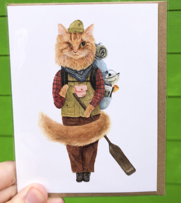 A cat dressed in the trappings of an explorer, complete with a stuffed backpack and a paddle in hand.