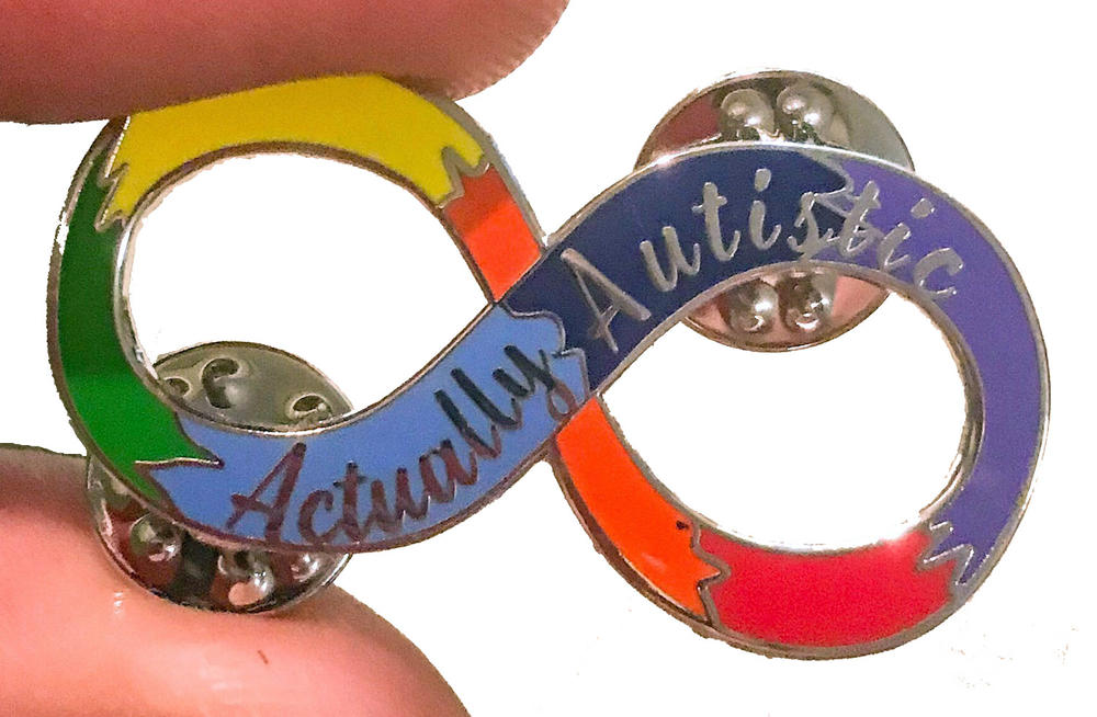"A rainbow of colors in the infinity loop with the words ""Actually Autistic"" on it."
