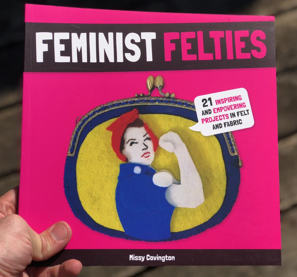 a felt cut-out of rosie the rivetter flexing