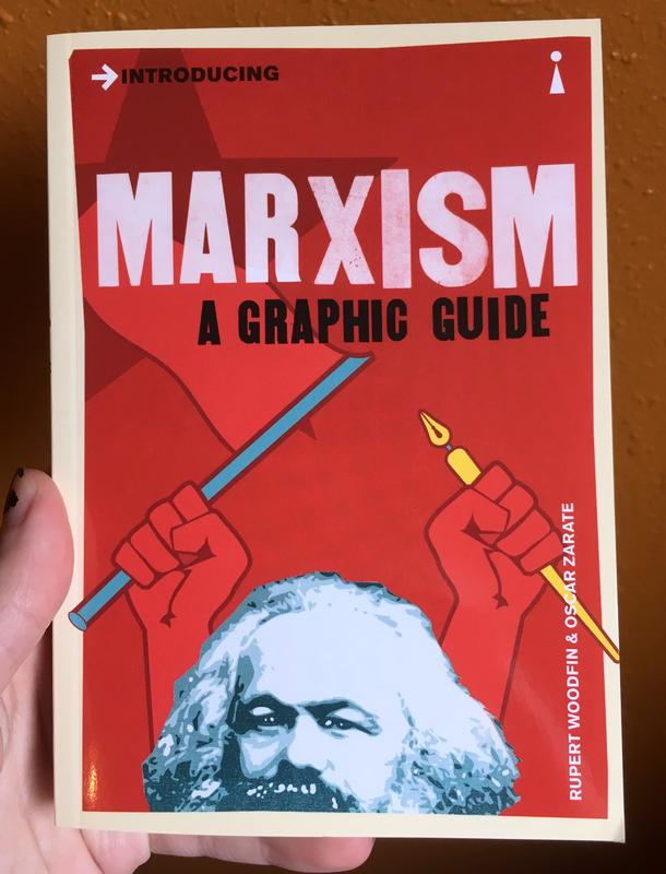 red book cover depicting karl marx's head and two hands holding a stick and a pen