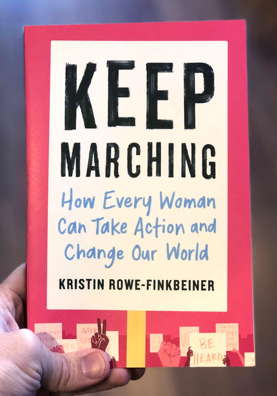 Image is the cover of Keep Marching: How Every Woman Can Take Action and Change Our World which is designed to look like the title is on a protest sign. At the bottom are other protest signs with common protest words and prhases, held up by hands of varying skin tones