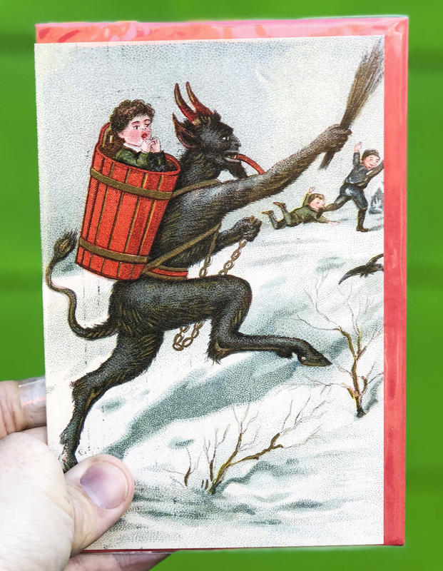 A devilish goat-like figure chases kids across the snow, a child in a barrel strapped to its back.