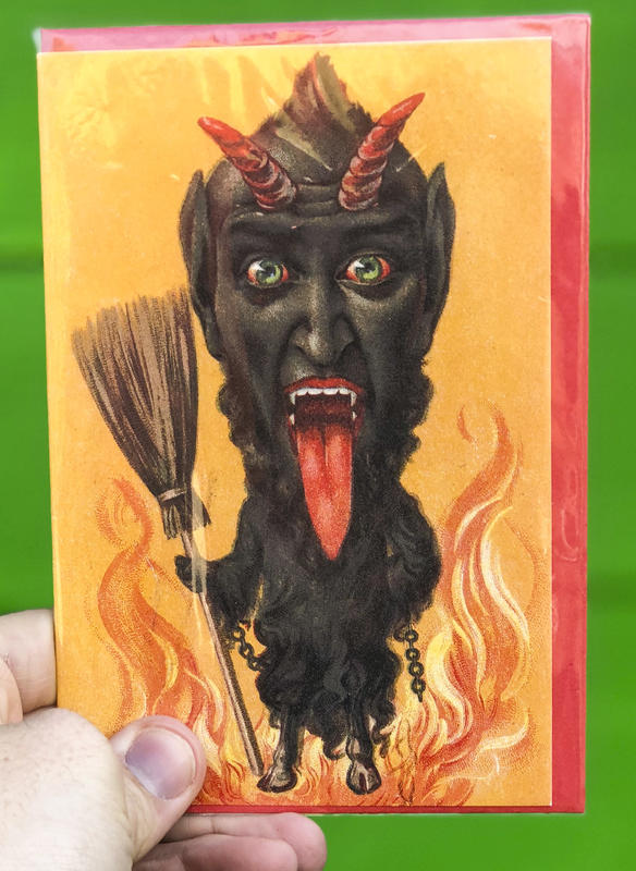 A devilish goat-like figure stands engulfed in flames, clutching a broom in his hand.