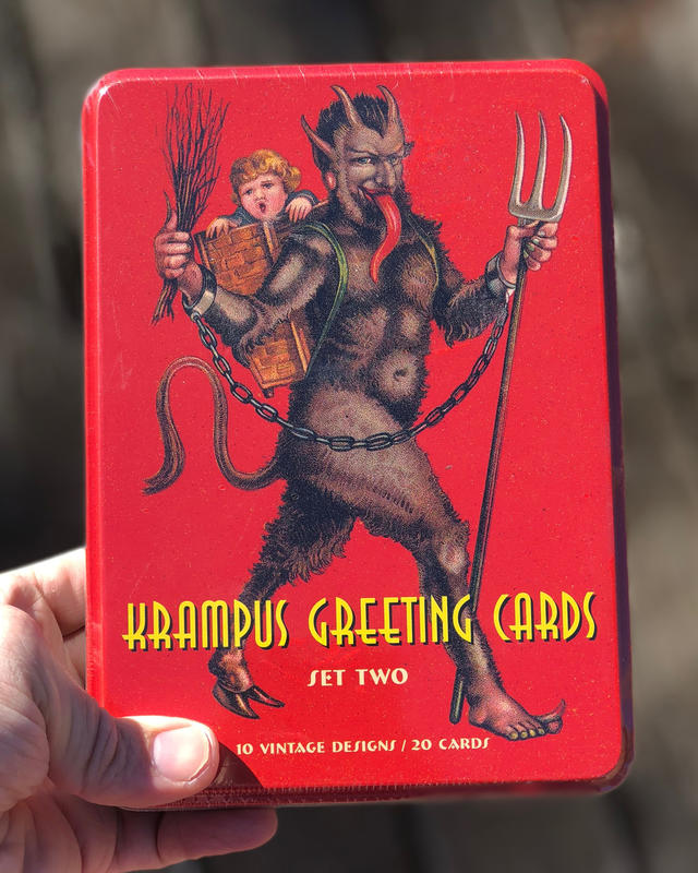 Krampus holding a pitchfork, with a kid in his back in a basket.