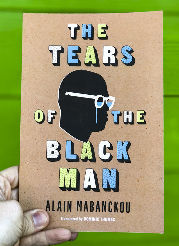 A silouhette of a black man crying, his glasses filled with his tears.