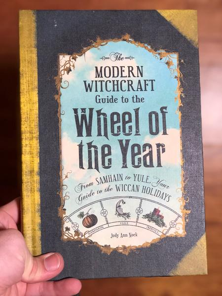 Modern Witchcraft Guide to the Wheel of the Year, The: From Samhain to Yule, Your Guide to the Wiccan Holidays by Judy Ann Nock [A cloudy sky drifts above a wheel of rotating pagan holidays]