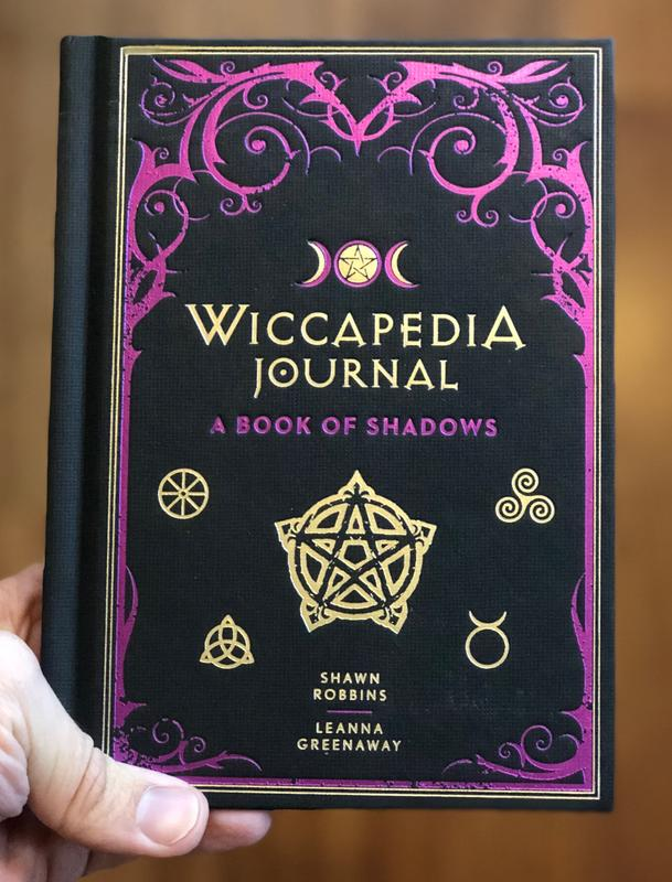 Cover of Wiccapedia Journal: A book of Shadows, which is black with purple and gold accents - primarily various pagan symbols