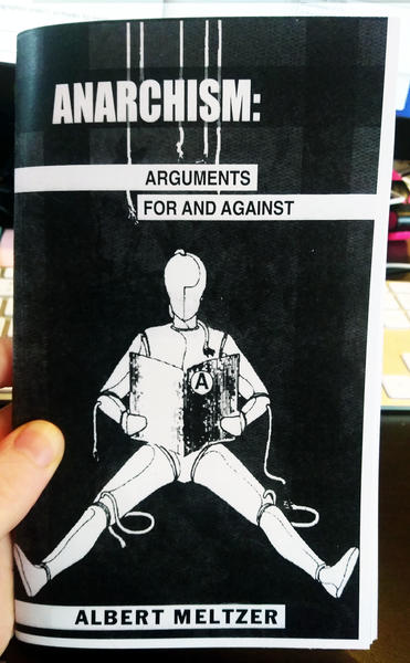 Cover of Anarchism: Arguments For and Against which features a white marionette with its strings cut readding a book with the anarchy A on the cover on a black background