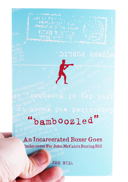 a light blue book with a small red boxer in the center and light white writing all over the blue background. Red writing states: Bamboozled - An Incarcerated Boxer Goes Undercover for John McCain's Boxing Bill