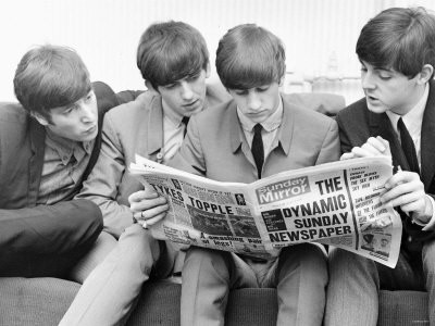The Beatles reading a newspaper
