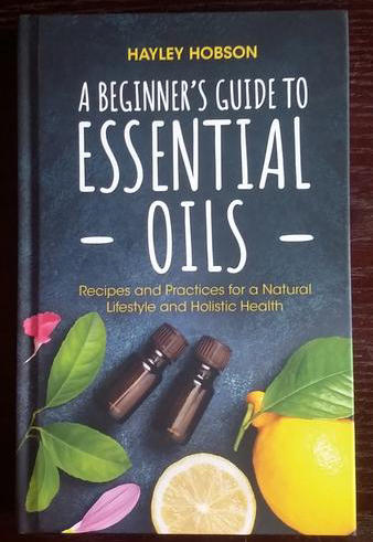 A Beginner's Guide to Essential Oils: Recipes and Practices for a Natural Lifestyle and Holistic Health by Hayley Hobson [Jars of oil surrounded by bright flowers and of course the requisite lemon]