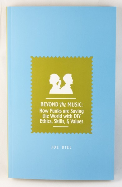 A light blue book with a green stamp and white silhouettes of a man and a woman, back-to-back