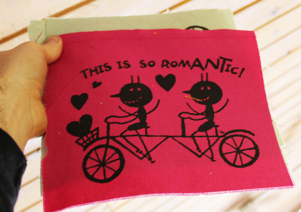"patch with image of two people on a tandem bike with hearts around them and the text ""this is so romantic!"""