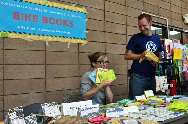 A photo of Microcosm's editor and publisher showing off the sweet bicycle books they made