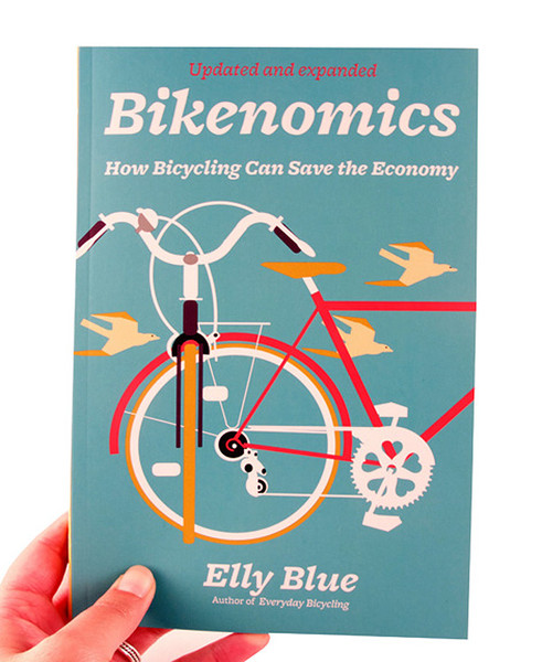 Blue book cover with two bicycles perpendicular to one another, birds fly behind them
