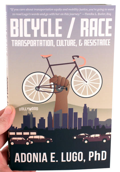 bicycle race book cover featuring a fist holding a bicycle above the LA skyline