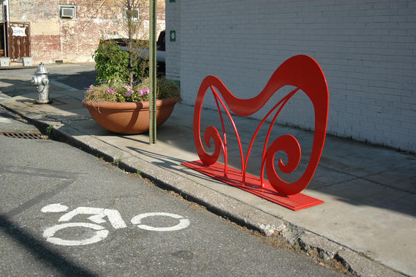 a photo of an artistic bicycle rack next to a bike lane