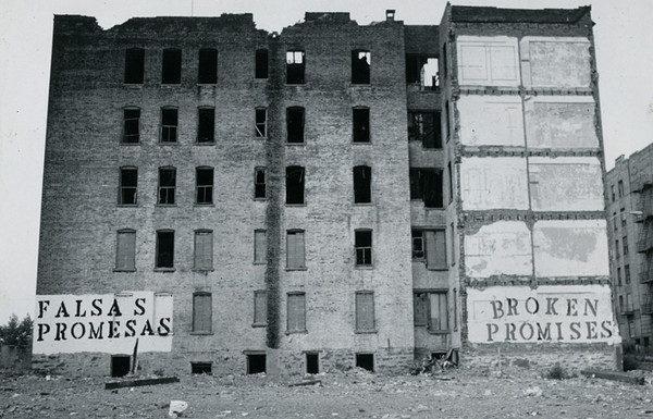 "blighted building with murals reading ""falsas promesas"" and ""broken promises"""
