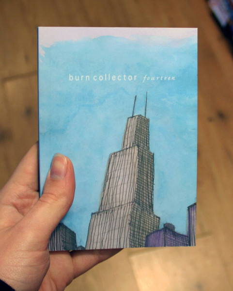 A blue book/zine with an illustration of a very tall skyscraper