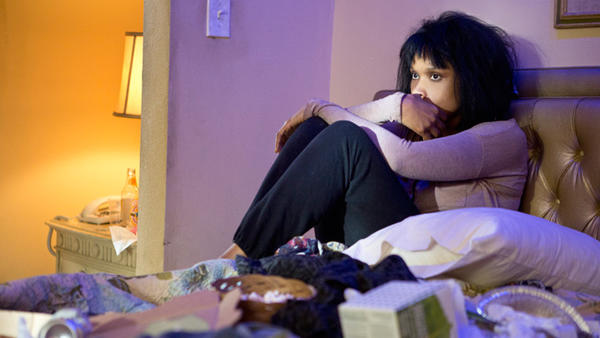 A movie still from Call Me Crazy showing a woman sitting on an unmade bed hugging her knees