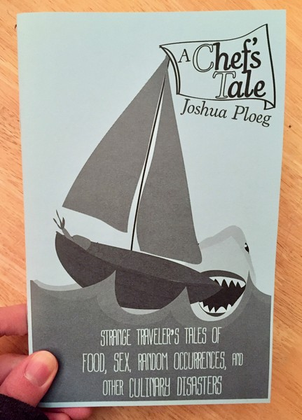 A zine with a shark taking a bite out of a small sailboat on the cover