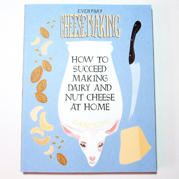 A blue book cover with illustrations of a goat, jar, nuts, a knife, and cheese blowup