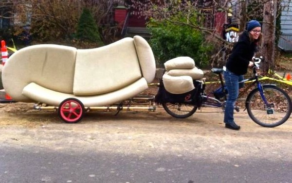 Photo of a person pulling a couch on a bicycle
