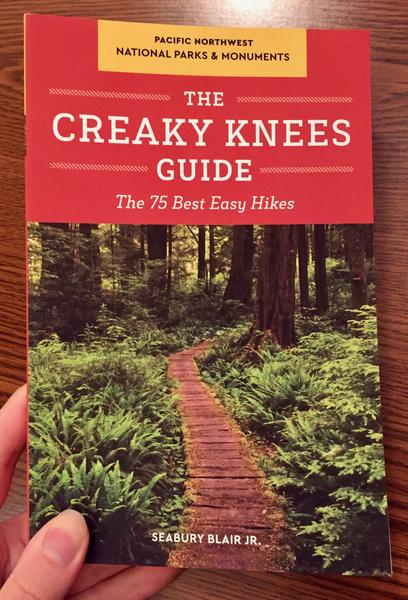 Creaky Knees Guide Pacific Northwest National Parks and Monuments: The 75 Best Easy Hikes [A wooden walkway meanders through a fern forest.]