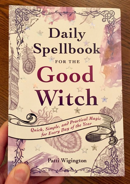 Cover of Daily Spellbook for the Good Witch by Patti Wigington which features ink drawings of feathers with splotches of purple and orange watercolor