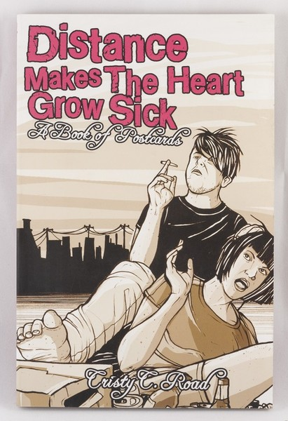 An emo looking couple sitting and smoking near the water with a pack of beer at their feet on a book cover