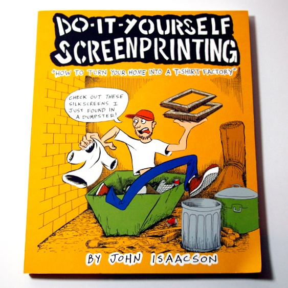 A yellow book with a cartoon of a man running from a dumpster with a t-shirt and silk screens in his hands