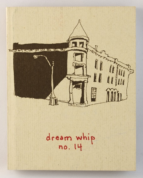 A small, white book with a sketch of an older building and a streetlamp