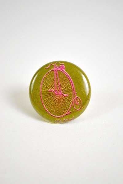 a button with a picture of a pennyfarthing bicycle and the words old school