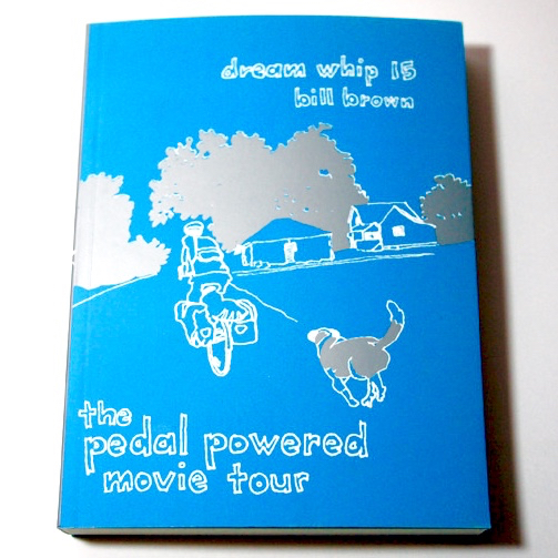 A blue book with an illustration of the back of a cyclist and dog riding/running down the road blowup