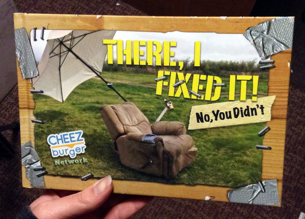 Cover of There I Fixed It!: (No, You Didn't) [A brown chair with a cupholder and umbrella attached sits in a green field.]