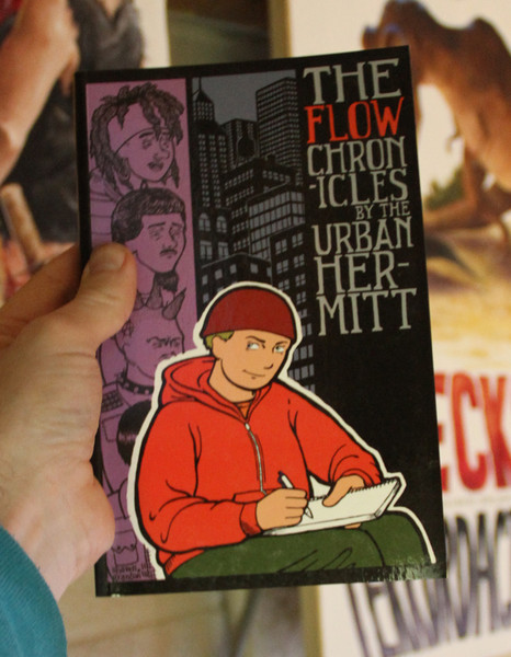 A black book with a drawing of a man in a red hoodie writing in a notebook