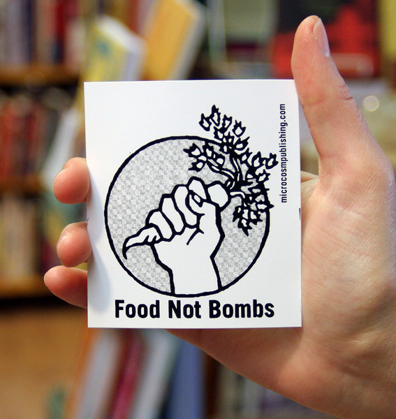 a hand holding a carrot with the words FOOD NOT BOMBS