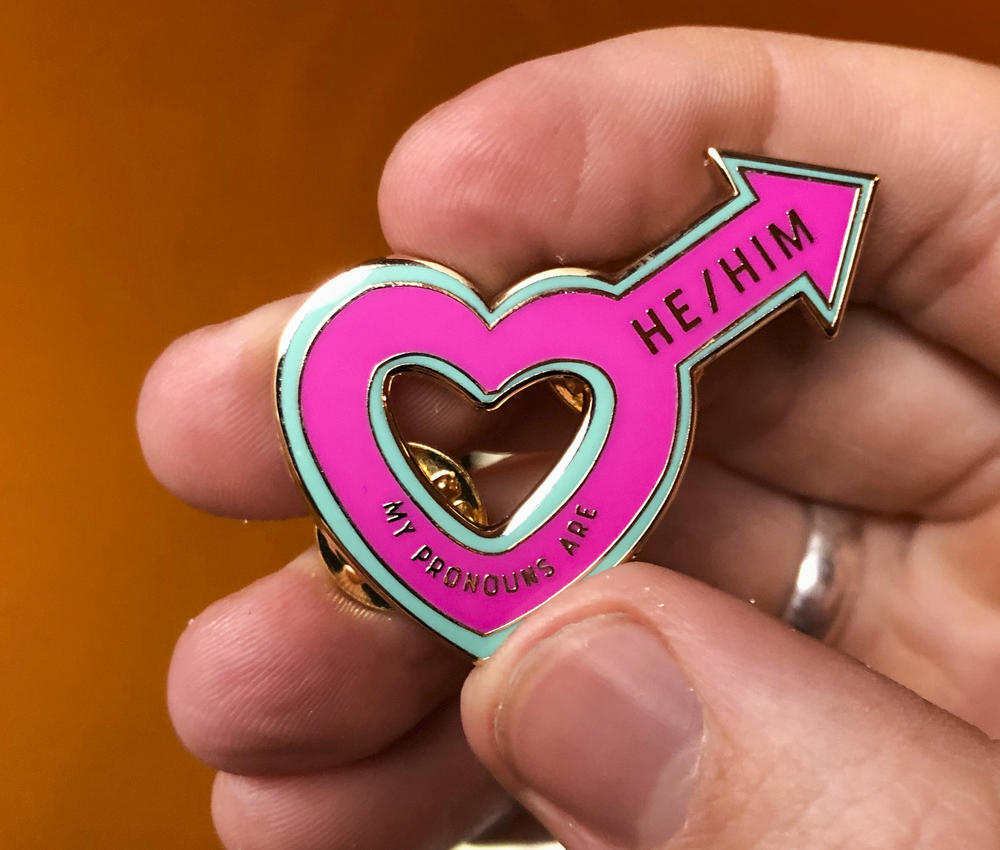 "An enamel pink male symbol in the shape of a heart with ""he/him"" written on it."
