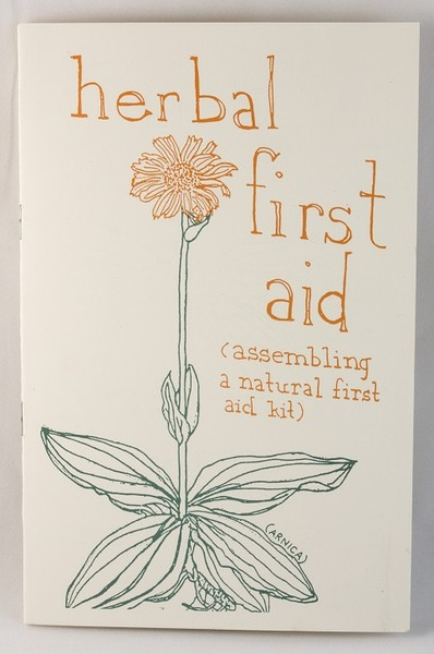 A white zine with an illustration of a yellow flower with a green stem and leaves