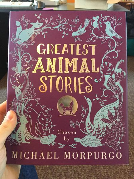 Greatest Animal Stories Chosen by Michael Morpurgo (light blue illustrations of all kinds of animals, including birds, a mouse, a turtle, a bunny and a small bear. A silver, howling wolf stands in front of a moon under the silver title, on a purple background)