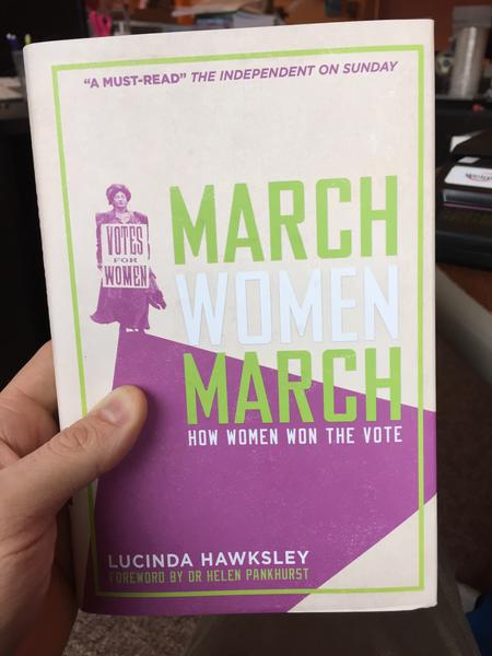 "A white and purple book cover with a woman holding a sign that says, ""Votes For Women."""