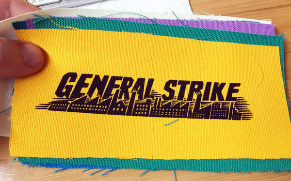 colorful patches printed with bold text and a backdrop of smokestacks