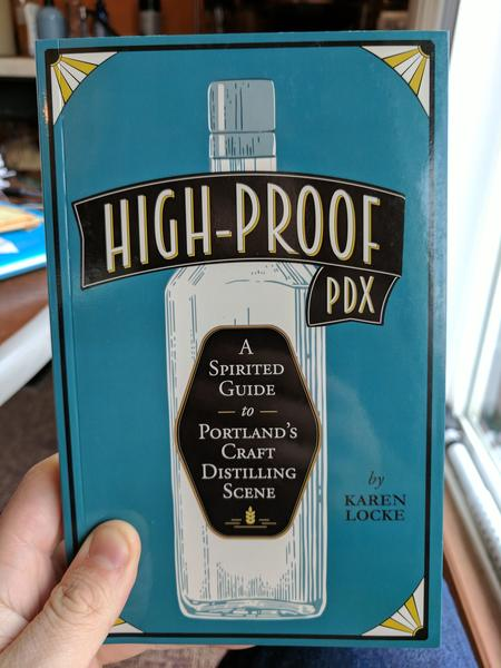 High-Proof PDX: A Spirited Guide to Portland's Craft Distilling Scene by Karen Locke (a blue background with gold and white corners. The title is sealed on a tall, glass bottle)