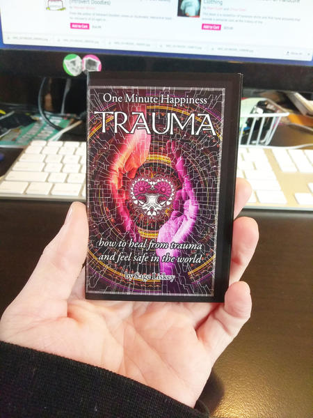 Cover of Trauma: How To Heal From Trauma And Feel Safe In The World (One Minute Happiness) which features two glowing purple/orange hands cupping a heart and chalice floating between them. blowup