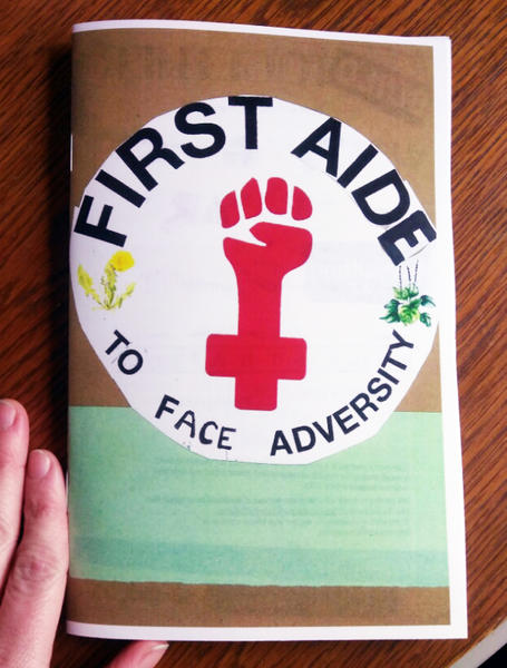 Cover of First Aide which features the power fist female symbol in red
