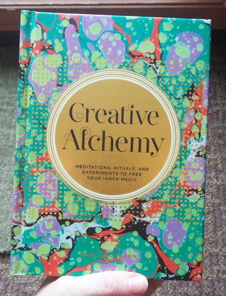 Cover of Creative Alchemy: Meditations, Rituals, and Experiments to Free Your Inner Magic which features the title in a gold circle on a multicolored abstract background.